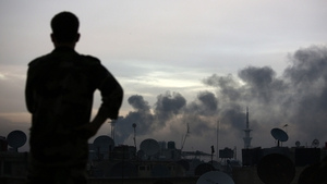 A man watches smoke rise from the Tall Kurdi region as he stands on the roof of his house in Douma