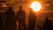 Kurdish people watch the sun set over Kobane from the southeastern village of Mursitpinar