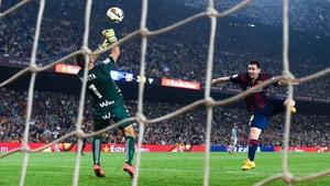 Lionel Mess heads the ball under a challenge by Xabi Irureta of Eibar