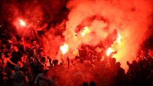 Galatasaray AS fans light flares after conceding a second goal during their side's Champions League match against Arsenal