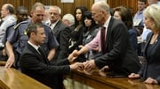 Oscar Pistorius shakes hands with family members before he was escorted to a holding cell