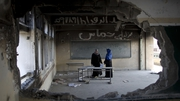 Palestinian teachers stand in a damaged classroom at a United Nations-run school in Gaza City