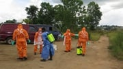A Red Cross burial team disinfects after recovering a number of bodies outside Freetown in Sierra Leone
