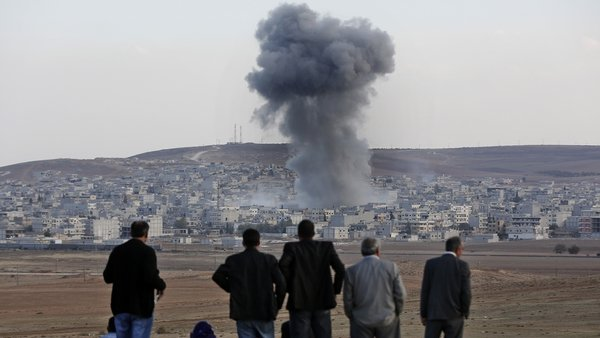 Local residents watch smoke from an explosion rising over the Syrian city of Kobane