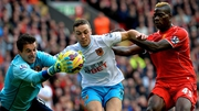 Hull City's goalkeeper Eldin Jakupovic and James Chester defend the ball from Liverpool forward Mario Balotelli