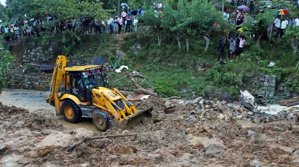The landslide area being excavated by a bulldozer as people watch during the rescue operation