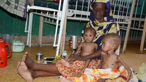 A mother sits with her two malnourished children in a hospital in Mogadishu