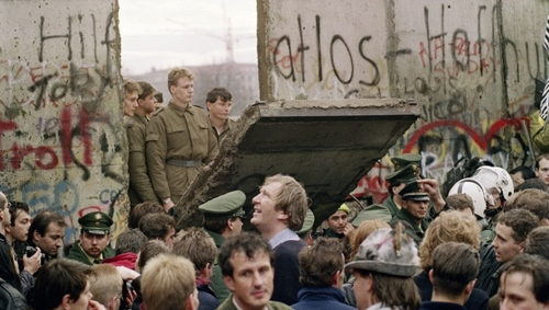East German border guards stand at a broken section of the wall in 1989