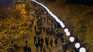 Visitors walk under a light installation of balloons tethered to lamps along the course of the former Berlin Wal