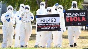 Protesters hold posters and clocks to represent time running out during an Ebola protest event in Brisbane