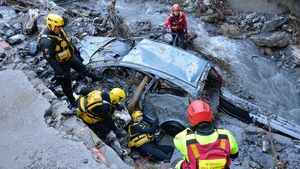 Rescue workers search for a missing person after torrential rain in Serra Ricco' near Genoa