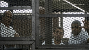 Peter Greste (L) and his colleagues, Egyptian-Canadian Mohamed Fadel Fahmy (R) and Egyptian Baher Mohamed pictured at their trial in June