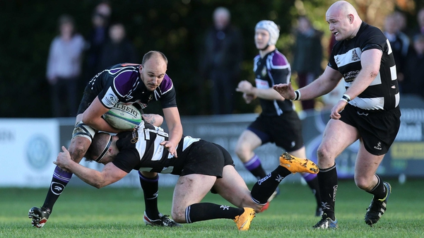 Kieran O'Gorman of Old Belvedere tackles Kyle McCoy