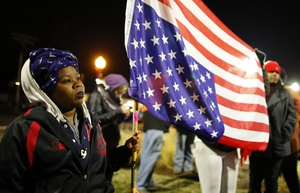 A protester holds an American flag outside the Ferguson Police Station