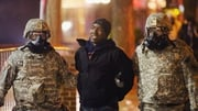 Two national guardsmen assist police during the arrest of a protester in Ferguson
