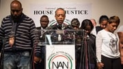 The parents of Michael Brown, left and right, bow their heads as they remember their son at a news conference in New York