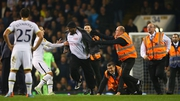 Roberto Soldado of Spurs and stewards apprehend a pitch invader
