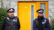 Police stand guard at a south London block of flats during an investigation into an alleged slavery case