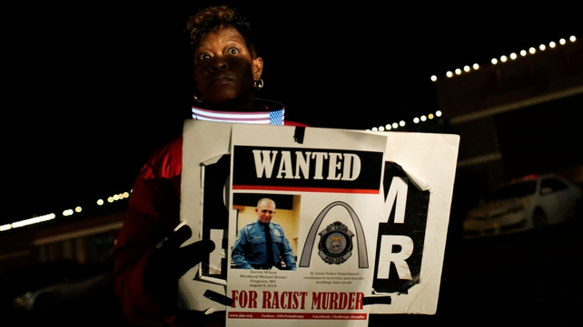 A demonstrator holds a 'wanted' poster of Darren Wilson