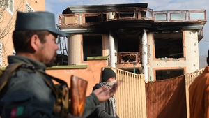 Afghan police stand outside the compound where four people died during Taliban attack