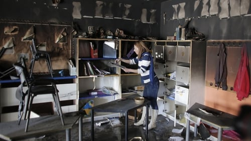 A woman inspects the damage inside the classroom