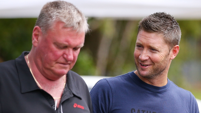 Australian cricket captain Michael Clarke (R) arrives with Michael Brown, working on behalf of Cricket Australia