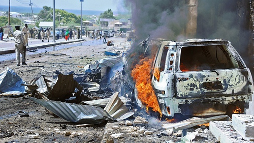 A car burns following the blast near the gates of the airport in Mogadishu
