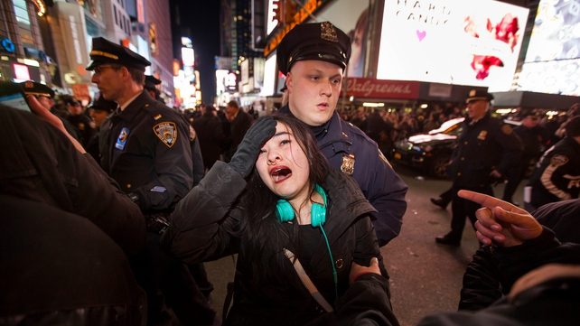 A woman reacts as New York City police officers push people out of an intersection in Times Square
