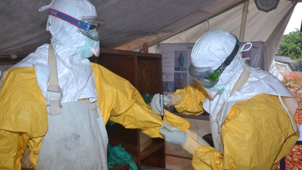 Health workers check each other's protective clothing at a treatment centre in Guinea