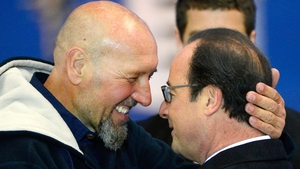 Serge Lazarevic is greeted by Francois Hollande at Villacoublay airport