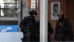Armed police stand near a café in the central business district