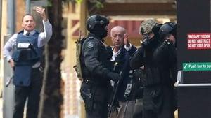 A hostage runs to safety outside the Lindt Café, Martin Place, Sydney