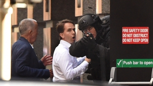 Escaped hostages take cover behind a police officer