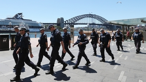 Police walk by the Sydney Harbour Bridge