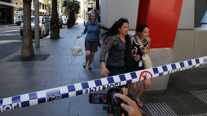 People rush out of Martin place as the area is evacuated