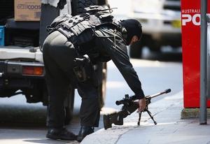 A police sniper sets up on Martin Street