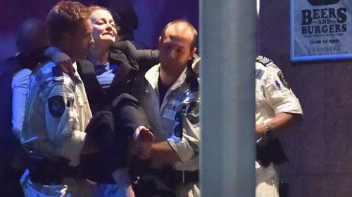 Rescue teams carry a woman out of the Lindt Café