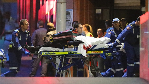 A person is taken out on a stretcher from the Lindt Cafe, Sydney