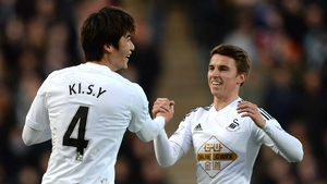 Ki Sung-Yueng of Swansea City celebrates scoring the opening goal with team-mate Tom Carroll