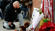 An NY police officer says a prayer while kneeling in front of memorial for the two deceased officers