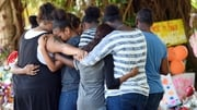 Mourners comfort each other while attending a floral tribute for the children