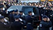 Police officers salute at the start of the funeral of New York Police Officer Rafael Ramos