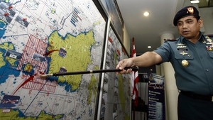 The Indonesian navy's Admiral Abdul Rashid points to a search area on a map
