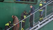 Passengers of the Norman Atlantic are helped down a gangway after a freighter ship picks them up