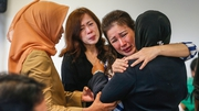 Relatives cry and comfort each other as they wait for news from the missing AirAsia plane