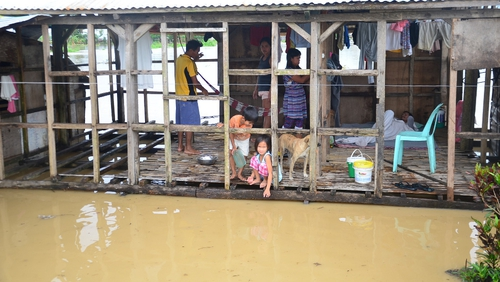A Filipino family inside their damaged house surrounded by floodwaters due to tropical storm Jangmi in Ormoc town, Leyte province