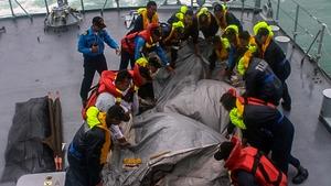 Crew of the Royal Malaysian Navy ship KD Lekir retrieve the emergency evacuation tube from AirAsia flight QZ8501