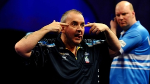 An animated Phil Taylor reacts after eventually sealing a dramatic sixth set at Ally Pally as a perplexed Vincent van der Voort looks on
