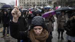 A young woman holds a symbol as she joins others gathered for a minute's silence in front of Notre Dame cathedral