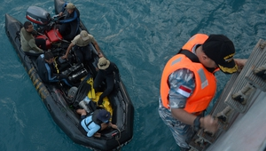 Indonesian Navy divers prepare to conduct operations to lift the tail of AirAsia flight QZ8501 in the Java Sea